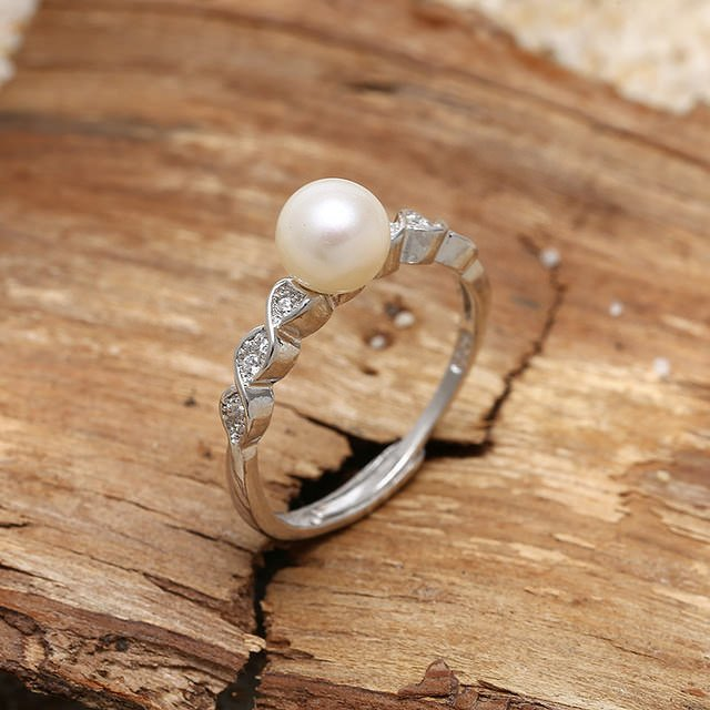 Pearl engagement ring with diamonds in gold setting.