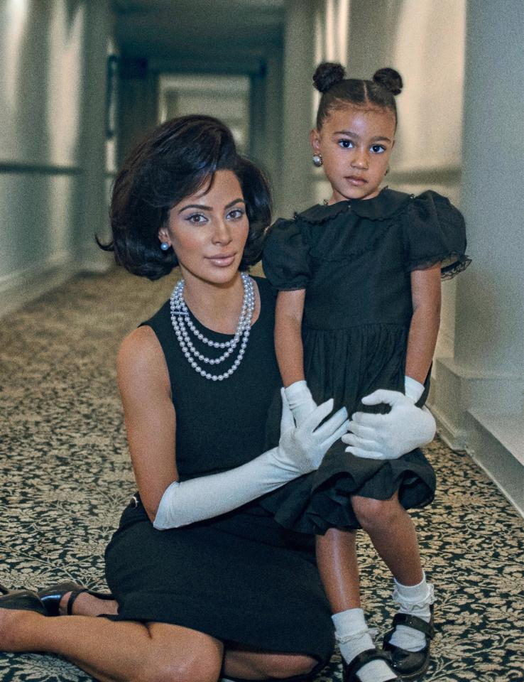 Kim Kardashian wearing a triple-strand pearl necklace and pearl earrings, with North West wearing big pearl earrings too.