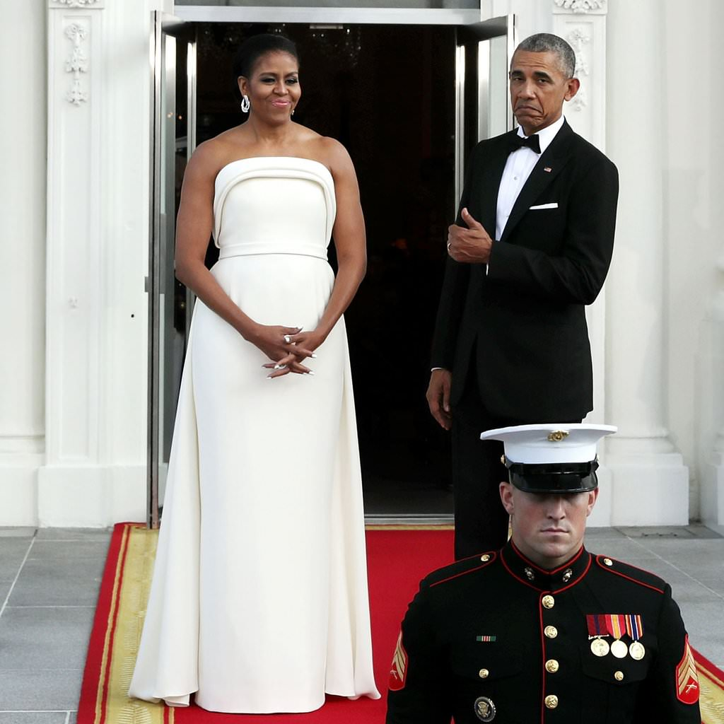 Former President Barack Obama gives his wife Michelle the THUMBS UP. She looks like American royalty in this all white gown at the State Dinner. (August 2016)
