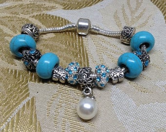 What a cute bracelet with its single white pearl and pretty blue trinkets.