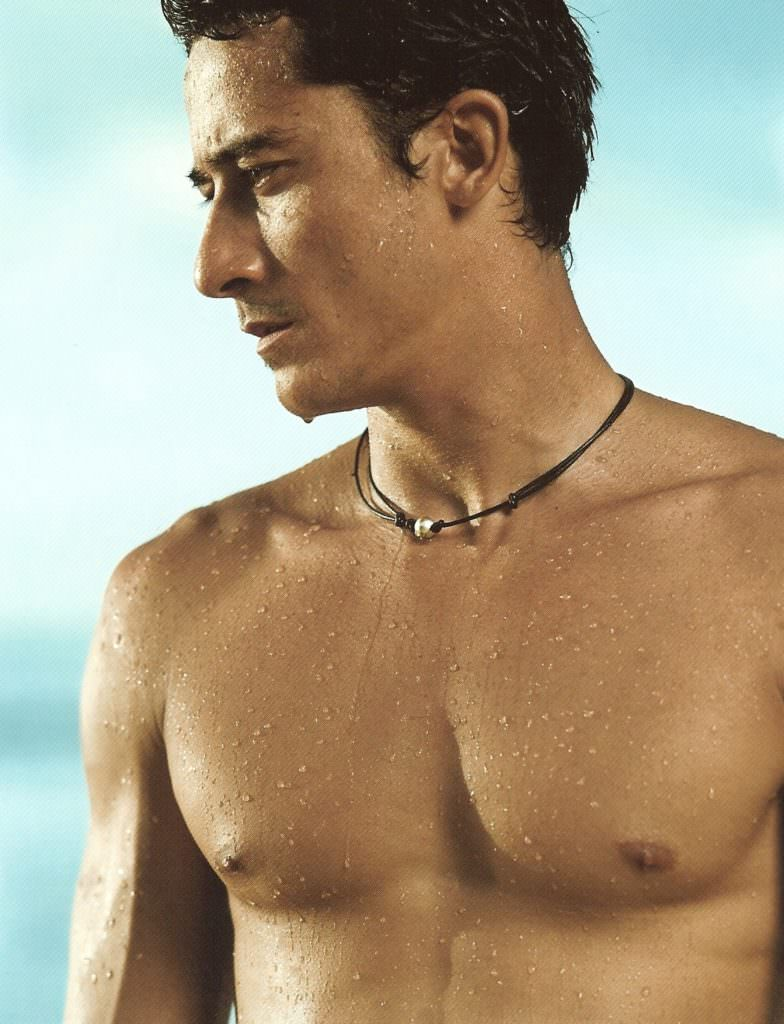 As he stands in the sunlight staring at the blue sea... wearing a leather necklace with a single pearl...