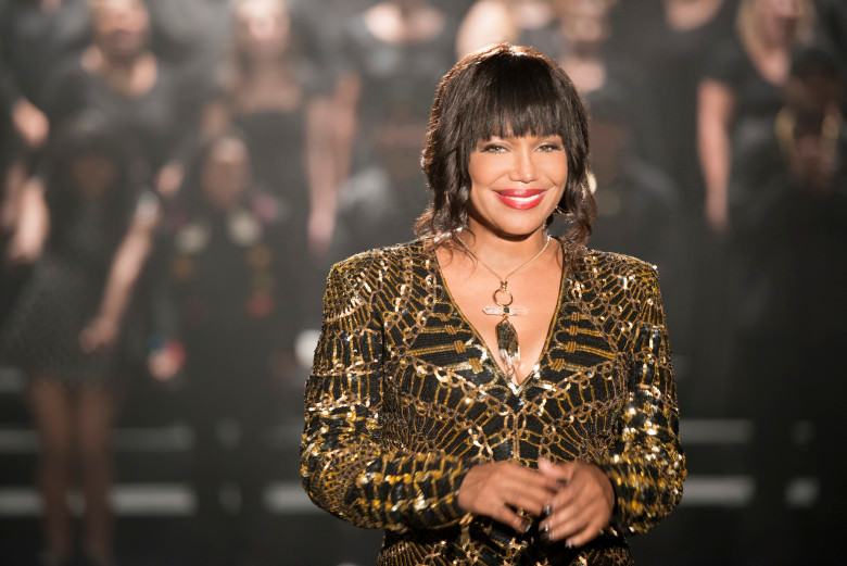 Michel'le's smile is as radiant as she looks in this black and gold piece with large statement-style necklace.
