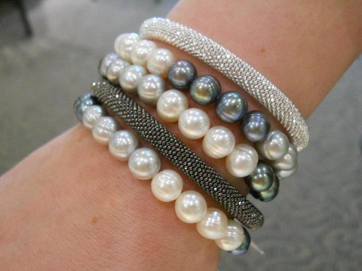 Pearl and metal bracelets layered.