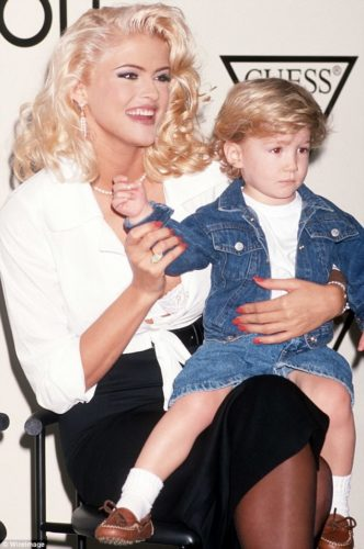 Anna Nicole Smith wearing a strand of pearls and dangling pearl earrings. That's her son Daniel (RIP) sitting on her lap.