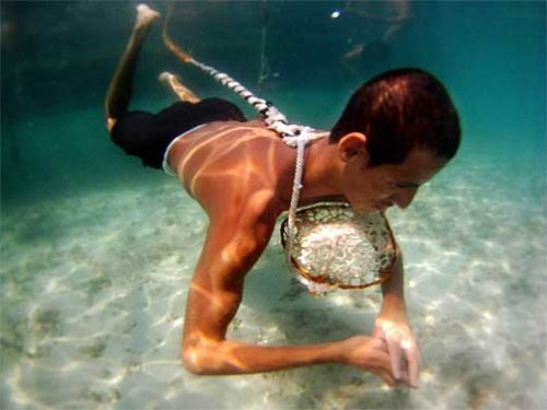 Man uses rope and basket to help with his pearl diving venture.